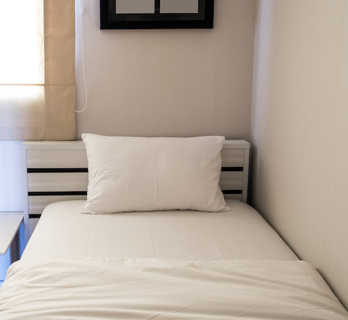 white blanket and pillow on bed in bedroom surtiespuma3